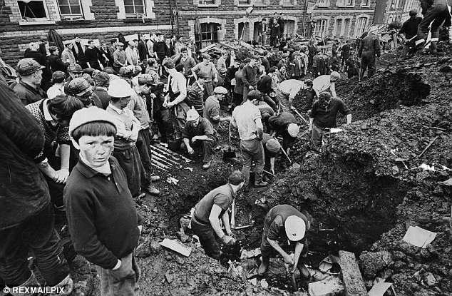 Horror: Rescue workers desperately dig through the mound to get to survivors after the mining disaster