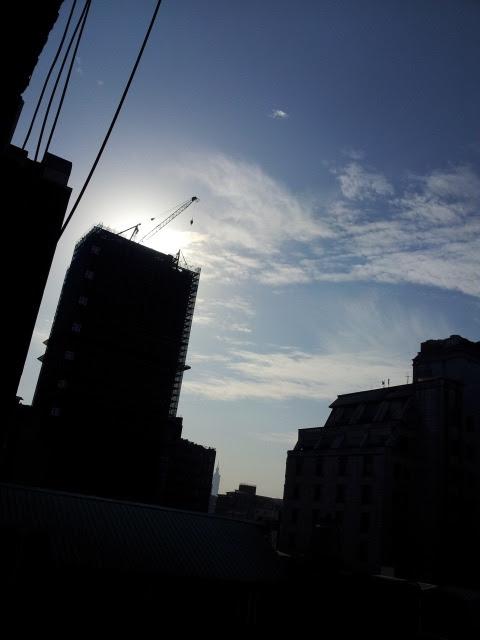 Taipei: Sun rises in the skyline of Linsen North Road 台北: 摩天楼から陽は昇る… 朝出かけ際に窓の外を覗くと建設中のマンション頂部から太陽が覗こうとしていた。間もなく彼岸である。これからは春秋と彼岸になるとこの建物から陽が登ることになる。 昨年もここに住んでいた。マンションの建設は始まったばかりで、姿かたちもなかった。いやそれ以前に低い建物、用途に覚えはないが、あたりの町並みとそろって立っていたような気がする。林森北路より道幅のある一本隣の中山北路で、古びた建物の建て替えがおこなわれていても四十五メートル止まりだ。 友人の建築家に、中山北路より狭い道幅の林森北路で、八十メートル高の建物建設は許されるのかと問うと、壁面後退、道路より壁面を後退させて仮想道路巾を広げ、それによって可能なのではと答えた。彼もこの場所より南、実現はしなかったものの、より繁華街に近い場所で計画を練っていたことがある。 私の部屋からは種々雑多な高さの建物が眺められる。大通りに囲まれ、街区の中心、ヘソ辺りの四階建てに始まり、外端に向かって、五階、八階、十二階、十四階と、まるですり鉢の様を呈している。さらに二十三階が加われば…今のところ、南に面し、陽もあたるし、風通しもよく、眺めもいい。文句はない。そして暗闇の残る、下町情緒ある一角が近場で活きつづけてくれればそれでいいのです。 *ちなみに私の部屋は八階、高さおよそ二十五メートル 写真中央下部あたりに薄い灰色で101ビルが写っている