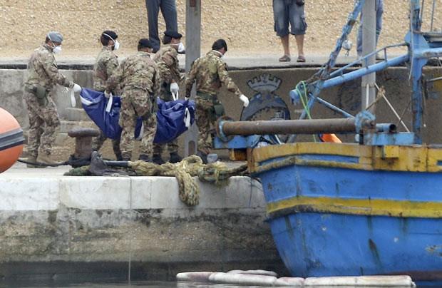 Soldados italianos carregam corpos de vítimas do naufrágio neste domingo (6) em Lampedusa (Foto: Reuters)
