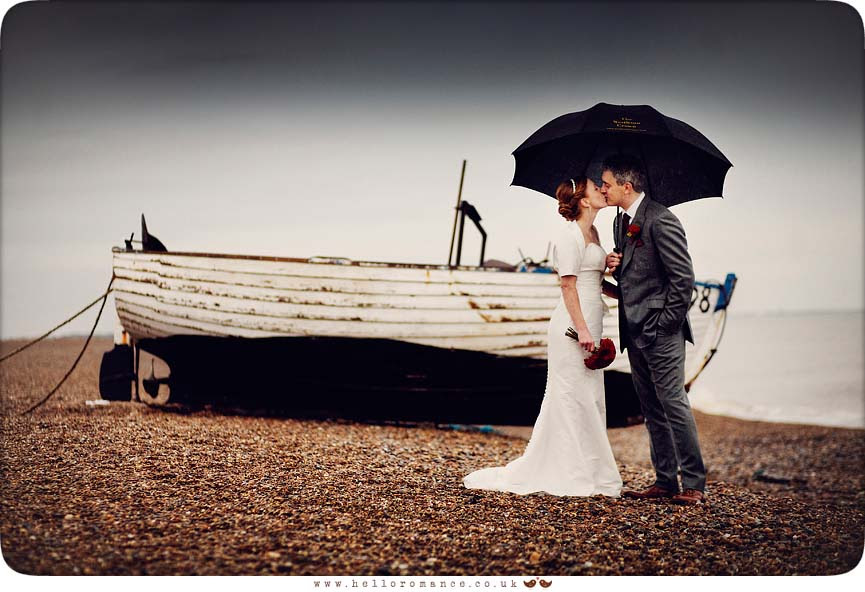 Bride and Groom kissing in rain on Dunwich Beach with umbrella and boat - Westleton Crown Wedding Photography - Kate and Rob - Hello Romance Wedding Photography Suffolk