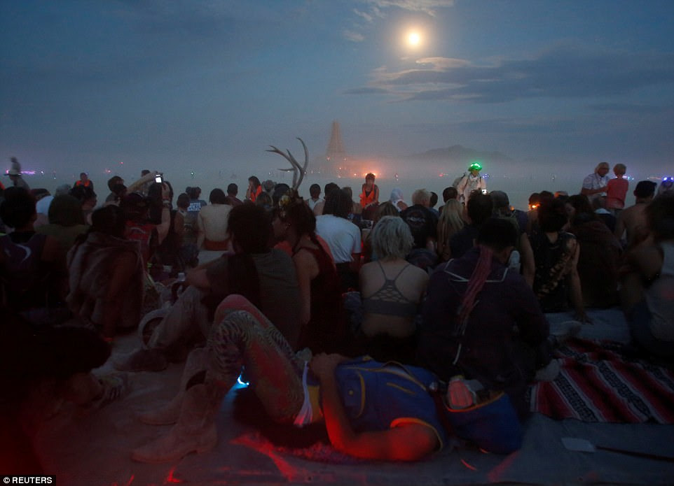 Revelers dressed in weird and wonderful attire congregate in the desert waiting to see the enormous pyre go up in flames