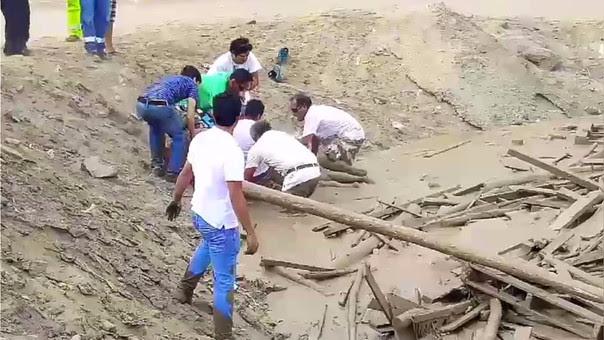 Momento en el que los vecinos de Punta Hermosa ayudan a salir del lodo a Evangelina Chamorro.