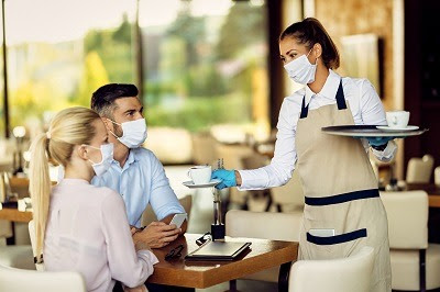 two friends at restaurant with server wearing masks