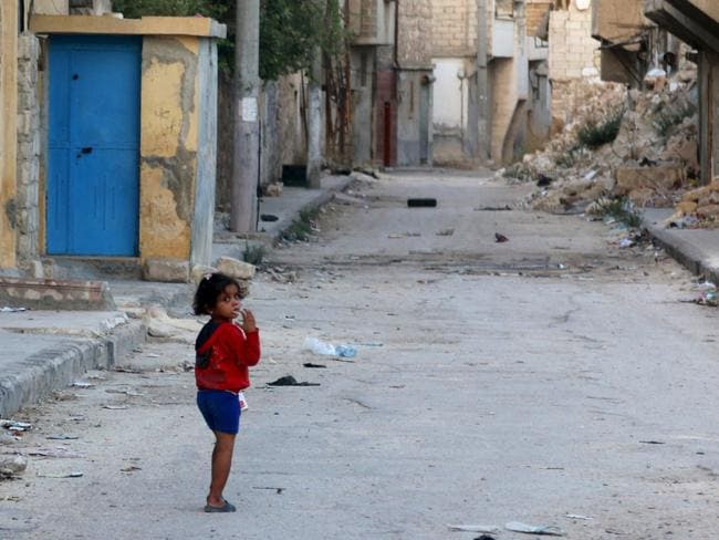 A girl walks along a deserted street in Tariq al-Bab neighbourhood of Aleppo, Syria. Picture: REUTERS/Abdalrhman Ismail