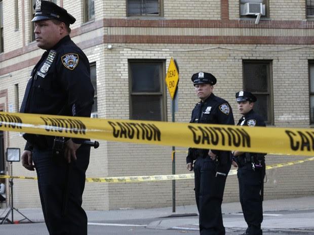 Policiais são vistos em frente a um prédio no bairro do Bronx, em Nova York, de onde uma menina de seis meses foi atirada da janela, na quinta (15) (Foto: AP Photo/Mary Altaffer)