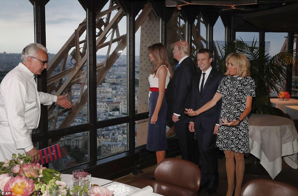 Le chef français Alain Ducasse, à gauche, geste les présidents et leurs femmes à leur table au restaurant Jules Verne à la Tour Eiffel à Paris, en France