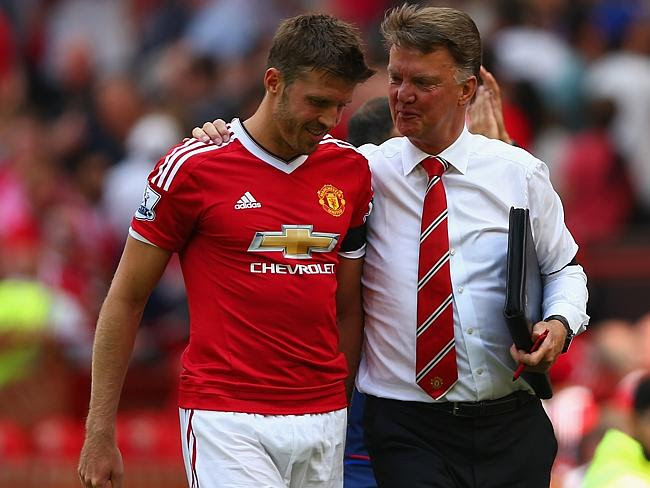 Michael Carrick of Manchester United walks with Louis van Gaal.