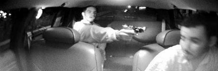 Security camera photo of a young robber pointing a gun at a taxicab driver