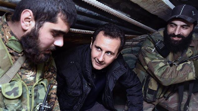 Cette photo de l'agence officielle syrienne SANA montre le président syrien Bachar-Al-Assad en discussion avec des militaires.