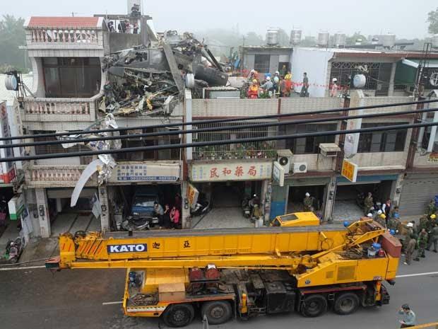 Duas pessoas - piloto e um militar - ficaram feridos após um helicóptero Apache, de fabricação norte-americana, cair no telhado de um prédio em construção em Taoyuan, no norte de Taiwan, nesta sexta-feira (25). O Acidente ocorreu durante um treinamento de rotina. (Foto: Sam Yeh / AFP Photo)