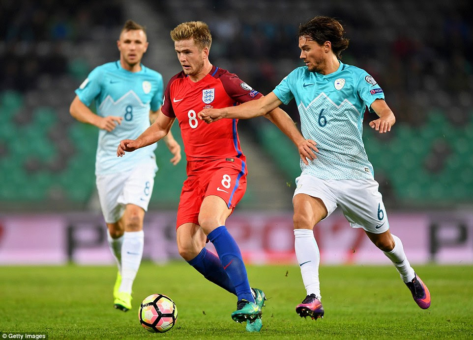 Eric Dier looks up to find a pass to a team-mate under pressure from Slovenia's defensive midfielder Krhin (right)