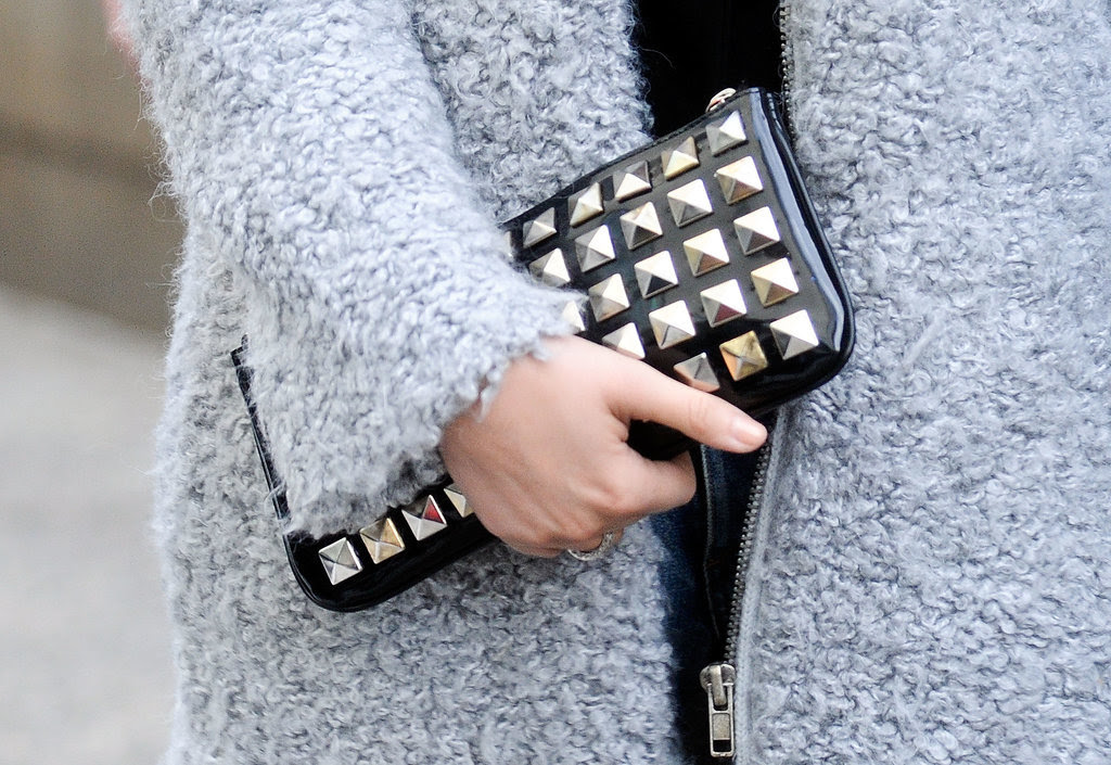 We're all about the contrast between a bouclé coat and tough-girl studded clutch.