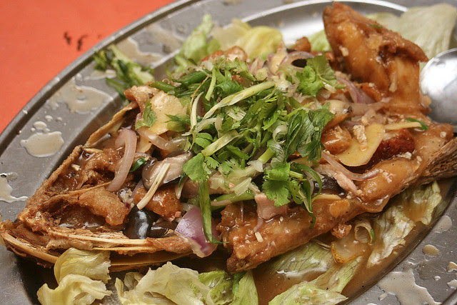 Fried fish head with lots of ginger, scallions, onions and mushrooms