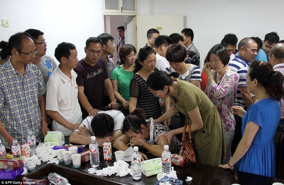 Grief: This picture taken on July 7, 2013 shows family members of Wang Linjia, one of the two teenage girls killed after a South Korean passenger jet crashed at San Francisco airport, grieving after they heard the news