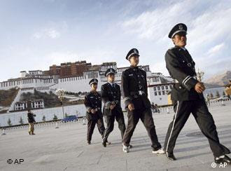Chinese security officers patrol a square with the Potala Palace, the Dalai Lama's former residence, seen at the background in Lhasa, capital of southwest China's Tibet Autonomous Region, China, Wednesday, March 26, 2008. The first group of foreign journalists allowed into Tibet since anti-government riots broke out has arrived in Lhasa on Wednesday. (AP Photo/Andy Wong)