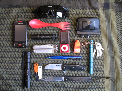 submitted by flecktarn  My EDC CRKT TUITION Cognet DOUK-DOUK (French knife) Fenix LD10 Fenix L2D Leatherman Wave Ipod Nano + Sennheiser earbuds Fox 40 Sonic Blast whistle Swith & Wesson tactical pen Light my fire Firesteel Light my fire Spork Kubotan Keychain ESS ICE glasses Smartphone Not on the picture a king cobra paracord bracelet (I forgot to take it out of my wrist) PS: Thanks for your awesome blog!  Editor's Note: Looks like a very hefty load out, but you'd be prepared for most… If you had to, I feel like you could ditch/swap one of the lights out, as the LD10 and L2D are virtually the same light but with different runtimes/brightness.. You might find more versatility in a keychain light with a different beam profile, tint, method of activation, etc. The two Fenixes seem redundant as a primary/backup set. Otherwise, nice carry — the Douk-Douk and kubotan look neat and all that color is less threatening while offering visibility. Thanks for sharing~