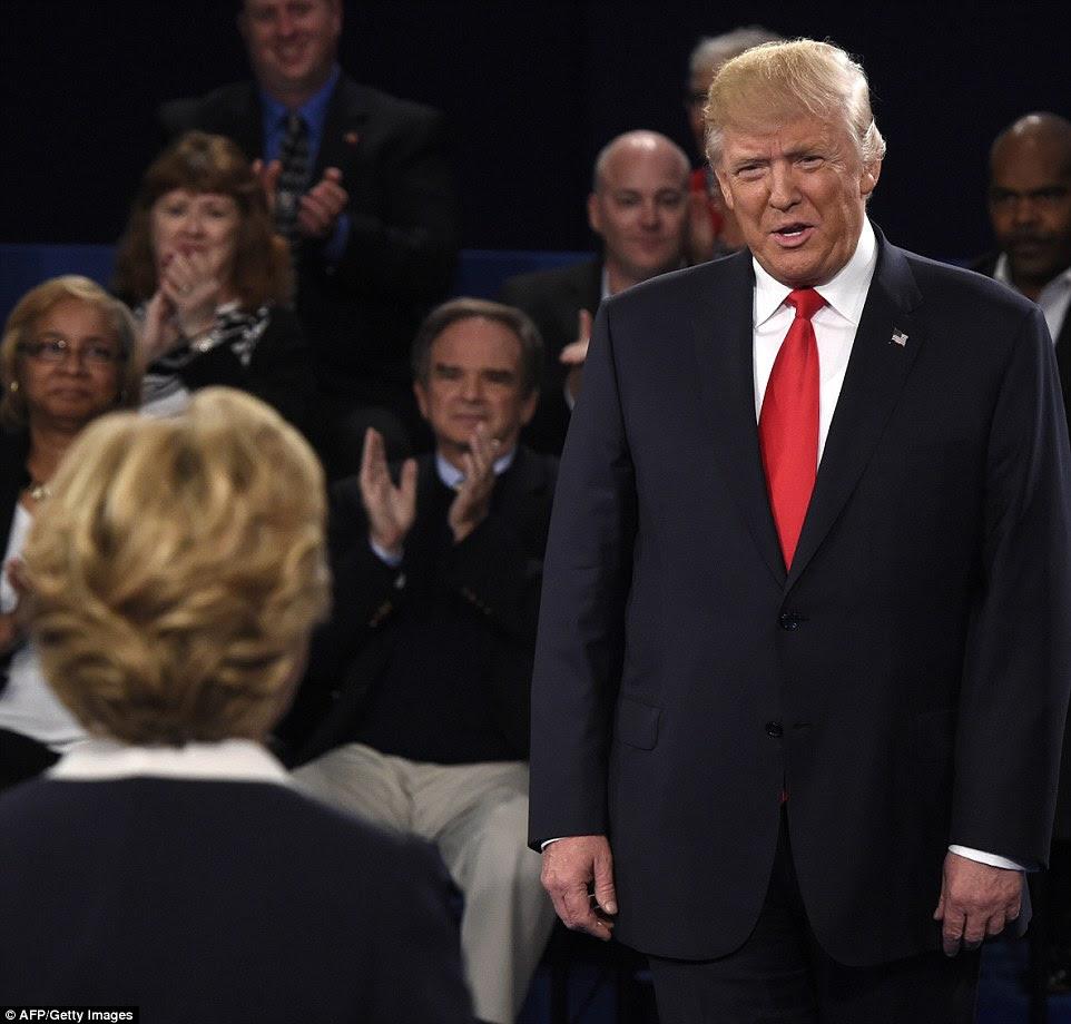 Hillary Clinton e Donald Clinton aparecem no palco debate como o público aplaude durante o evento da Câmara Municipal na noite de domingo