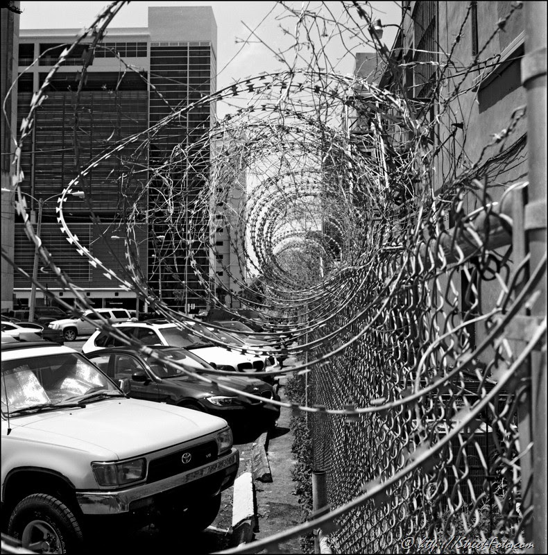 Black and White photographof barber wire at SW 1st street in Downtown Miami, Florida, USA, 2010. Street Photography of Miami, San Francisco and Key West by Emir Shabashvili, see http://street-foto.com, http://miamistreetphoto.com, http://miamistreetphotography.com or http://miamistreetphotographer.com
