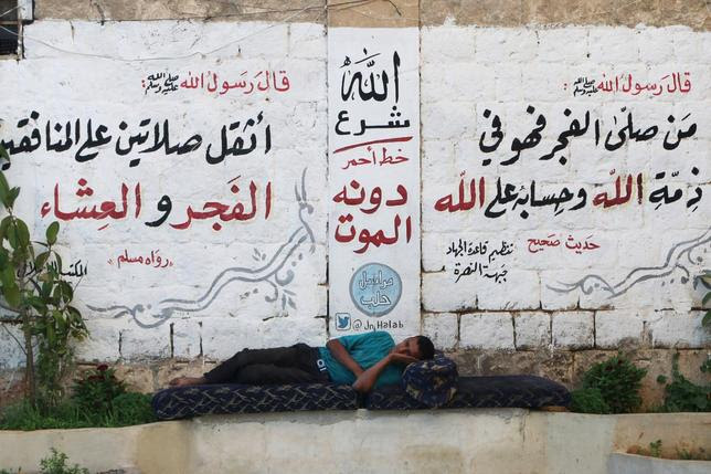 A man rests in front of a wall decorated with religious phrases written by members of al Qaeda's Nusra Front in Aleppo's Qadi Askar neighborhood, Syria July 13, 2015. REUTERS/Abdalrhman Ismail