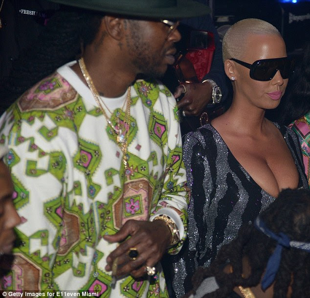 King bling: Amber looked to be hanging out with rapper 2 Chainz at the star-studded party. The 38-year-old put on an eye-catching display himself in cream, green and pink patterned jumper
