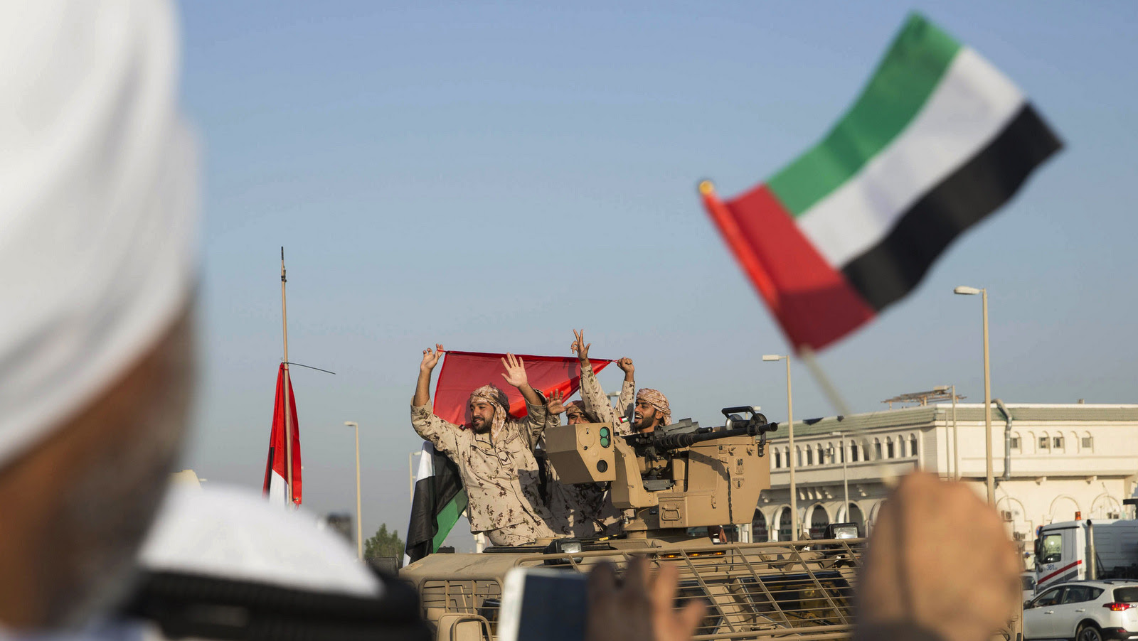 Emiratis wave the national flag as a convoy of  UAE military personnel return from fighting in Yemen, Nov. 7, 2015.  (Ryan Carter-Crown Prince Court/AP)