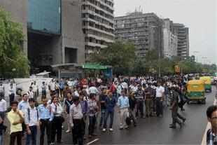 People wait for buses at Connaught Place in New Delhi.
