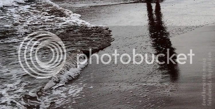 Una sombra reflejada en la orilla del mar cambiante