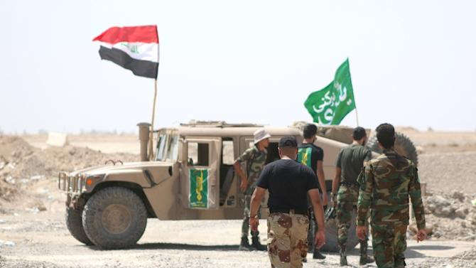 Members of the Popular Mobilisation units gather around a vehicle during a military operation against Islamic State (IS) group jihadists north of Fallujah, in Iraq's Anbar province, on August 19, 2015