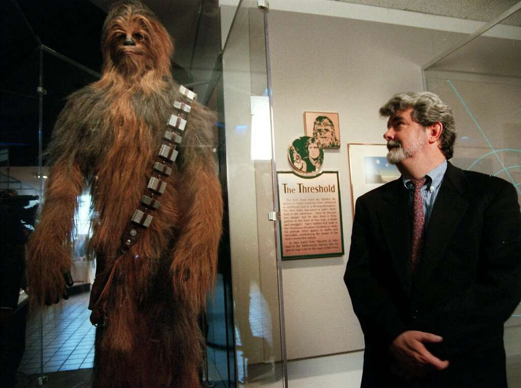 """Moviemaker George Lucas looks over Chewbacca at the """"Star Wars"""" exhibit at the Smithsonian Institution's Air and Space Museum in 1997. Photo: KEN CEDENO, AP"""