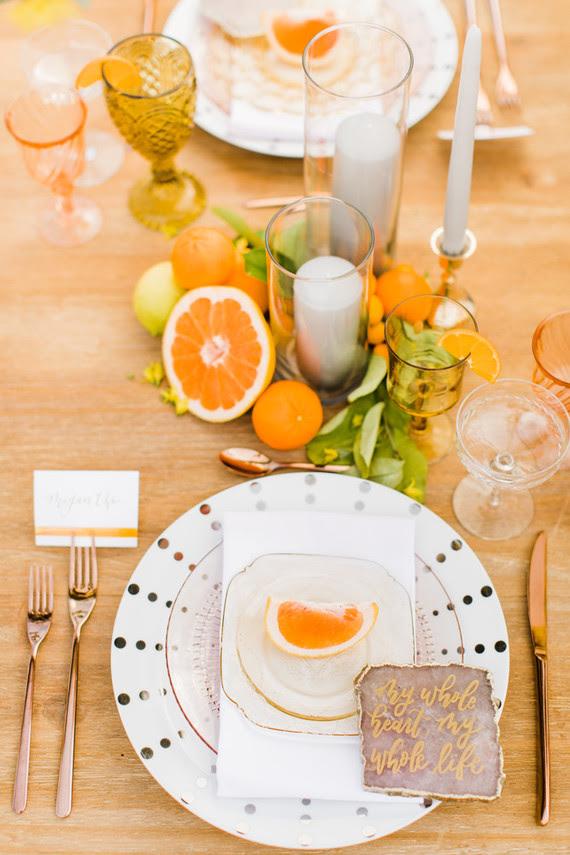 Die tablescape fertig war mit Kerzen und verschiedenen Arten von Zitrusfrüchten, polka-dot-Platten, Quarz-Scheibe Platz-Karten