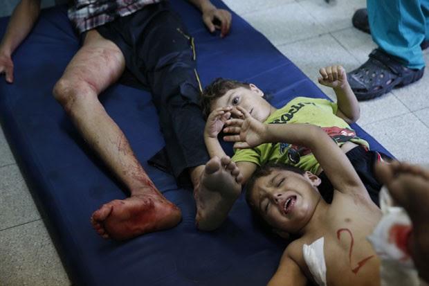 Crianças e homem ferido são vistos após ataque a escola da ONU em Beit Hanoun, no norte da Faixa de Gaza, nesta quinta-feira (24) (Foto: Lefteris Pitarakis/AP)
