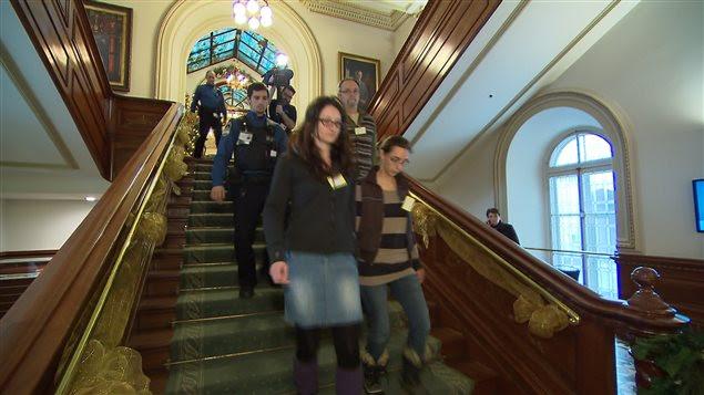 Des membres du groupe qui ont perturbé la période des questions escortés par des agents de sécurité.