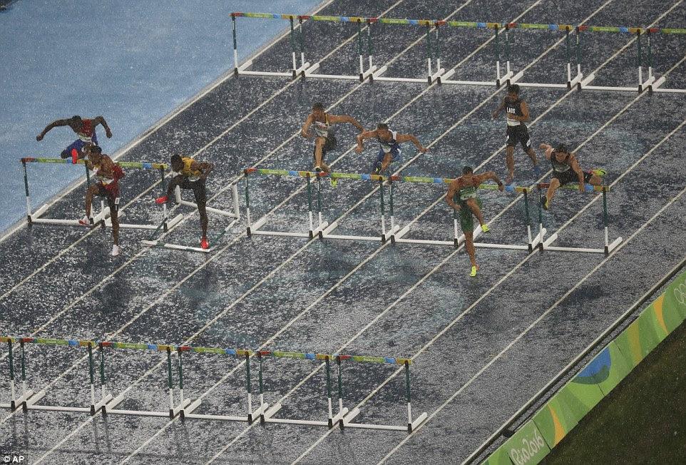 A chuva torrencial não pode parar os homens, que vão nos 100m aquece obstáculo, com os atletas lutando por condições difíceis
