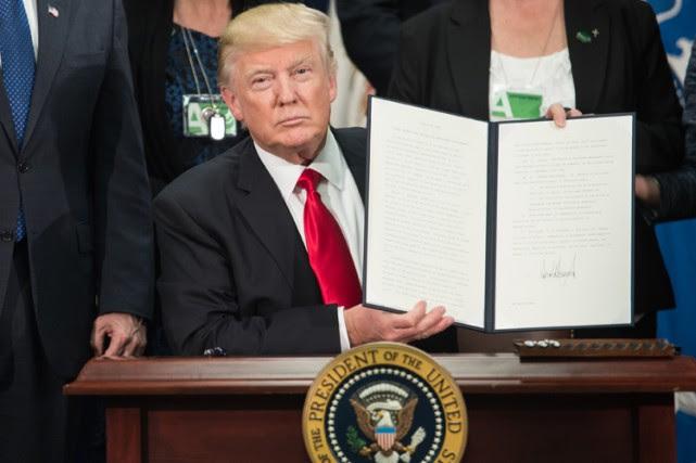 Donald Trump présente aux caméras sa signature sur... (PHOTO AFP)