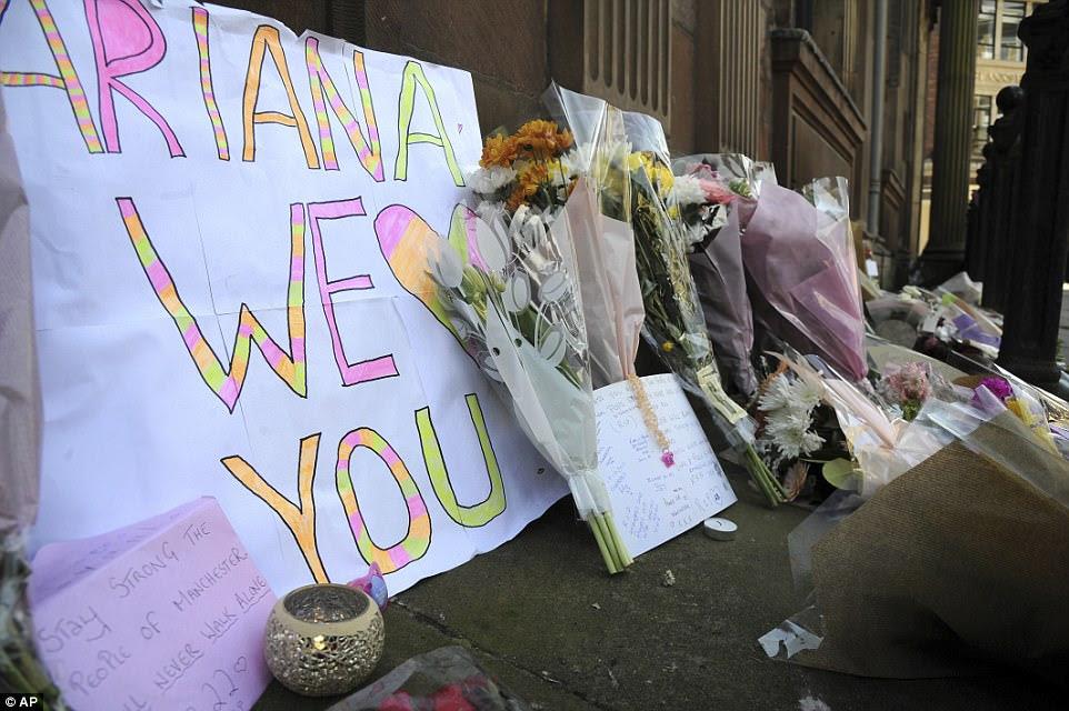 Um sinal que um jovem levou para o concerto foi incorporado a um mar de tributos florais na praça da cidade de St Ann