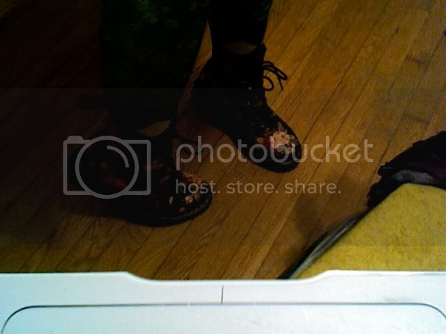 a pair of feet in flowered doc marten boots, standing on tiptoes
