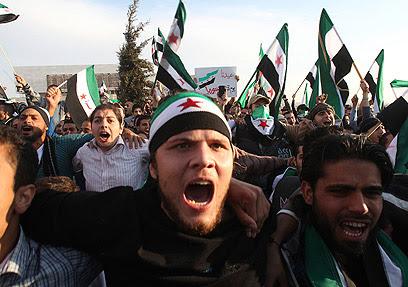 מפגינים עם דגלי סוריה המהפכנית ביום הקורבן (צילום: רויטרס)