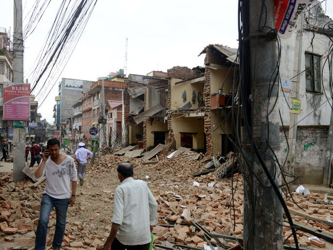 Nepalese people walk past collapsed buildings at Lalitpur,