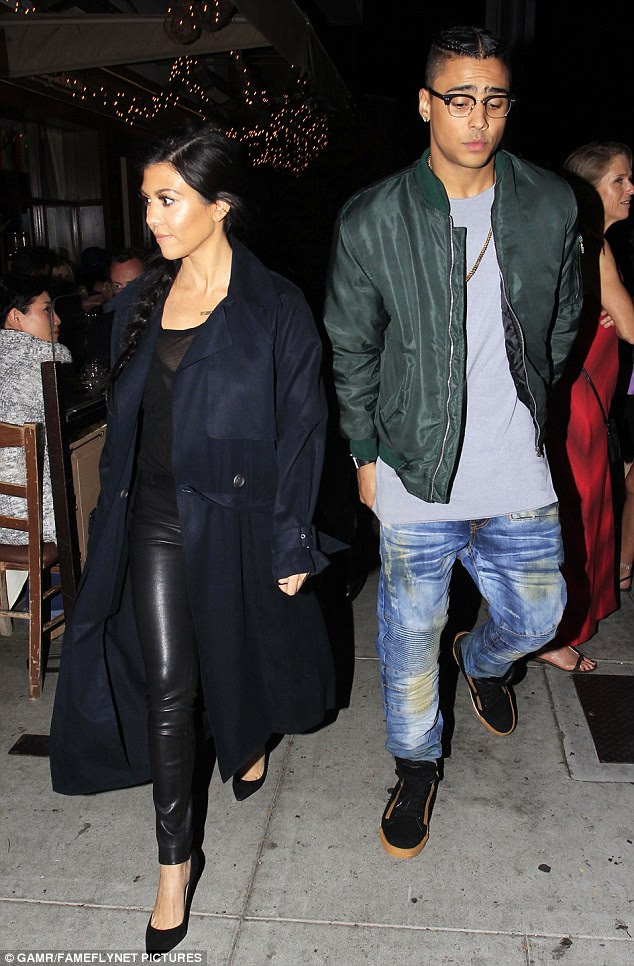 Fashion flare: Kourtney looked stylish in a navy trenchcoat over a sheer black top with matching leather trousers and heels