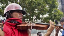 A young protester plays his violin in the streets of Caracas as national guards throw teargas and pellets.