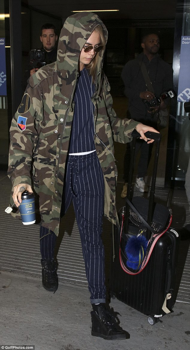 Looking cool:Cladding her 5 ft 8 in height in a matching pair of navy striped trousers and top, she walked forth in funky black trainers