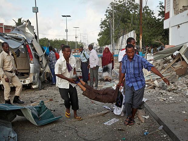 Homens carregam uma das vítimas das explosões perto de hotel na capital da Somalia neste domingo (1) (Foto: Farah Abdi Warsameh/AP Photo)