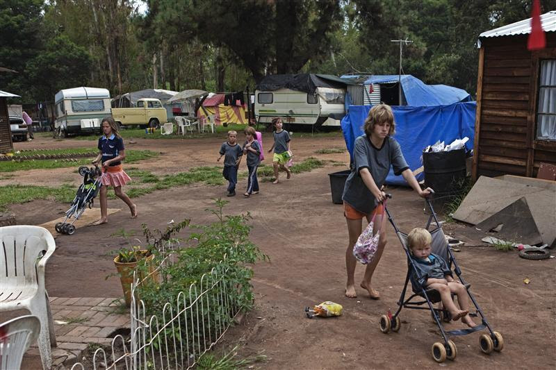Children walk through a squatter camp for poor white South Africans at Coronation Park in Krugersdorp, March 6, 2010. A shift in racial hiring practices and the recent global economic crisis means many white South Africans have fallen on hard times. Researchers now estimate some 450 000 whites, of a total white population of 4.5-million, live below the poverty line and 100,000 are struggling just to survive in places such Coronation Park, a former caravan camp currently home to more than 400 white squatters. Picture taken March 6, 2010. To match feature SAFRICA-WHITES REUTERS/Finbarr O'Reilly (SOUTH AFRICA)