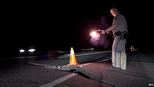 A California Highway Patrol officer redirects traffic from a buckled section of road