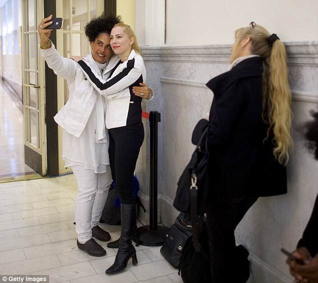 Cosby accusers Lili Bernard and Caroline Heldman pose for a selfie while waiting in line before the courtroom opens at the Montgomery County Courthouse on Thursday morning