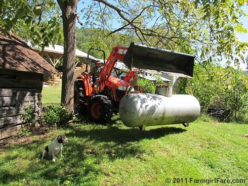 Joe uses the tractor to move the propane tank - FarmgirlFare.com