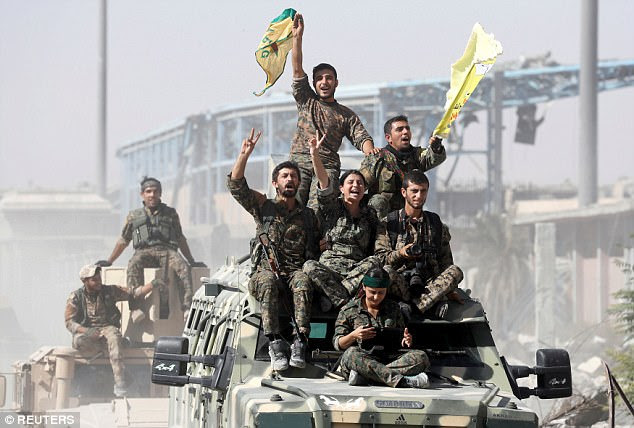 Thousands of jihadists fled to Turkey after the terror group lost its grip on the strongholds of Raqqa in Syria and Mosul in Iraq this year. Pictured: Syrian Democratic Forces (SDF) fighters ride atop military vehicles as they celebrate victory in Raqqa, Syria in October