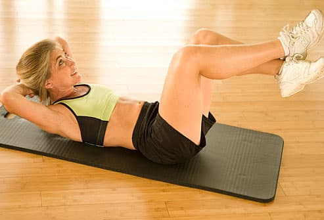 Trainer doing abdominal crunch, feet up