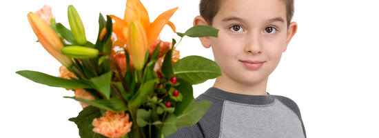Eight years old boy presenting flowers to someone, perhaps its National Teacher Appreciation Day