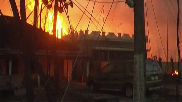 Chamas são vistas em casas após explosão em gasoduto na Índia (Foto: NNIS via AP Video)